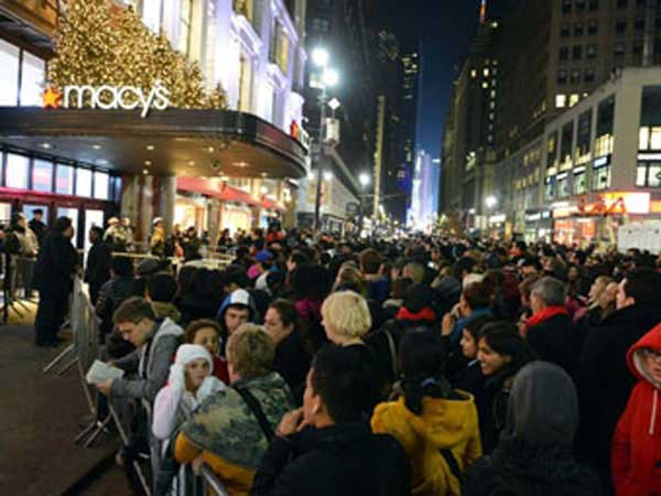 Shoppers at night waiting outside Macy's department store.