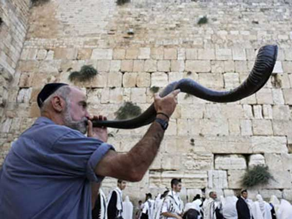 Man blowing the Shofar in front of the Western wall in Jerusalem.