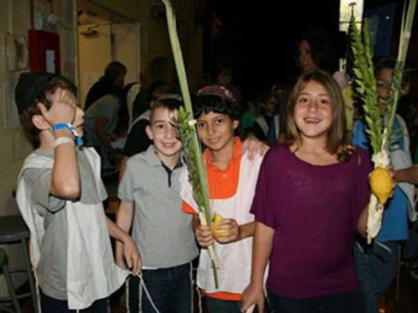 Children with squash and corn husks celebrating Shemini Atzeret.