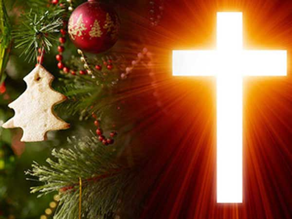 Glowing cross with decorated Christmas tree.
