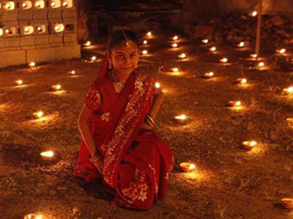Girl celebrates Diwali with diyas (oil lamps).