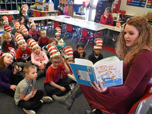 Teacher reads Dr Seuss book to children.