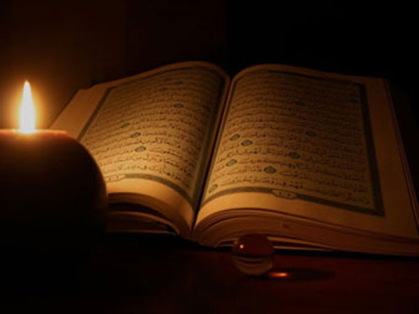 Koran lit by candlelight.