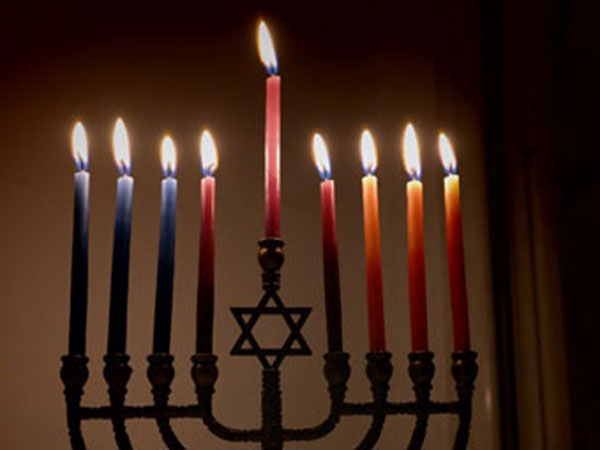 Colorful candles lit on the menorah for Hanukkah.