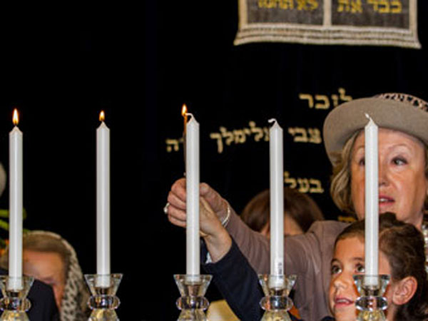 Mother and daughter light candles to commemorate Yom Hashoah.