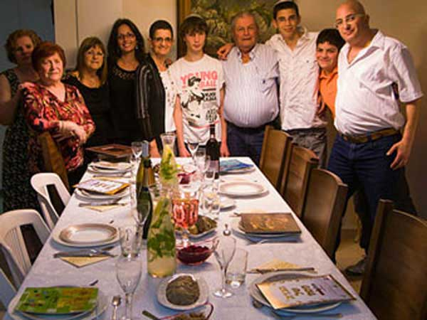 Jewish family in Israel sitting down to enjoy Passover dinner.