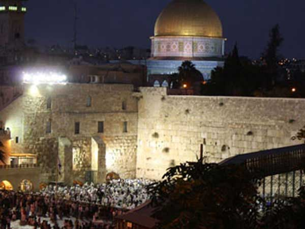 Jews praying at the western wall in Jerusalem at night for Yom Kippur.