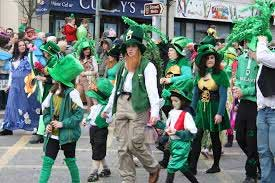 People walking in parade dressed in green with shamrocks