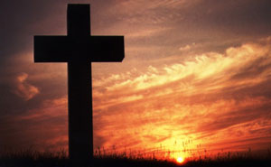 Large cross with setting sun behind